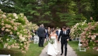 A bride and Groom walking up the path after saying I do at Seven Hills Inn