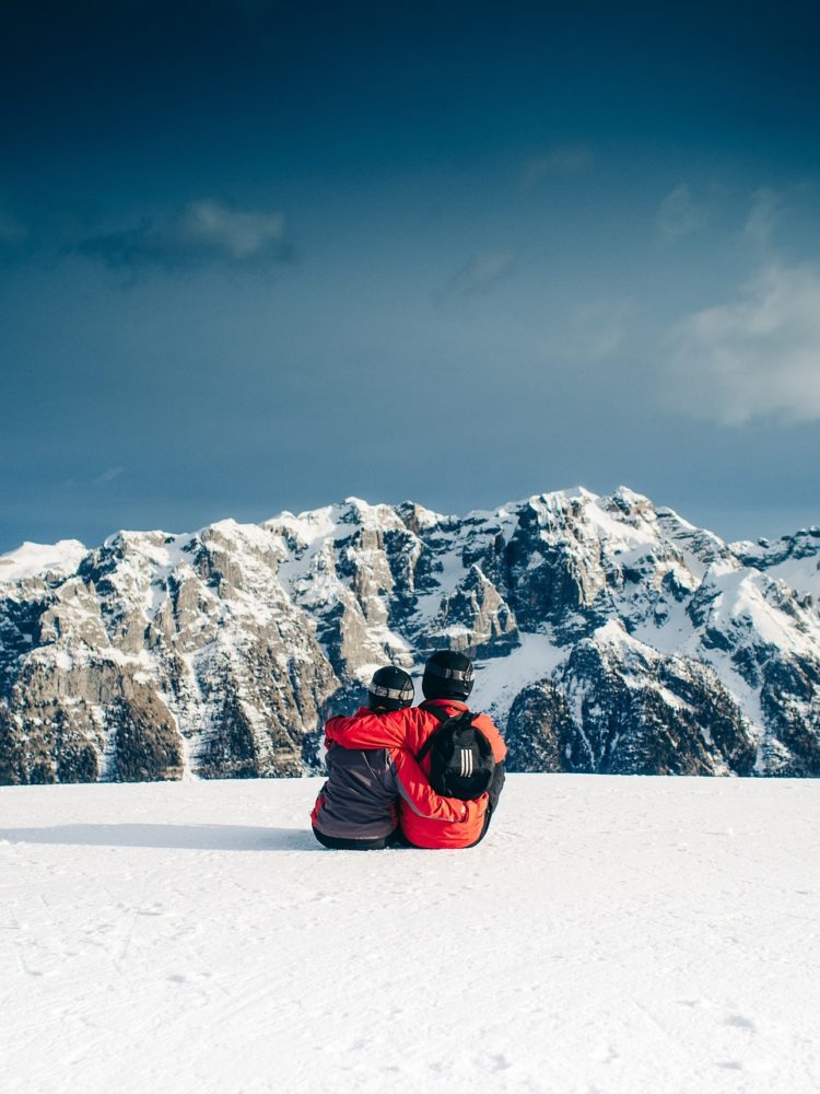 Couple sitting in snow looking at mountains together