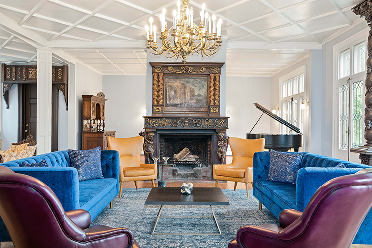 Plunkett Lounge sitting area with fireplace and grand piano.